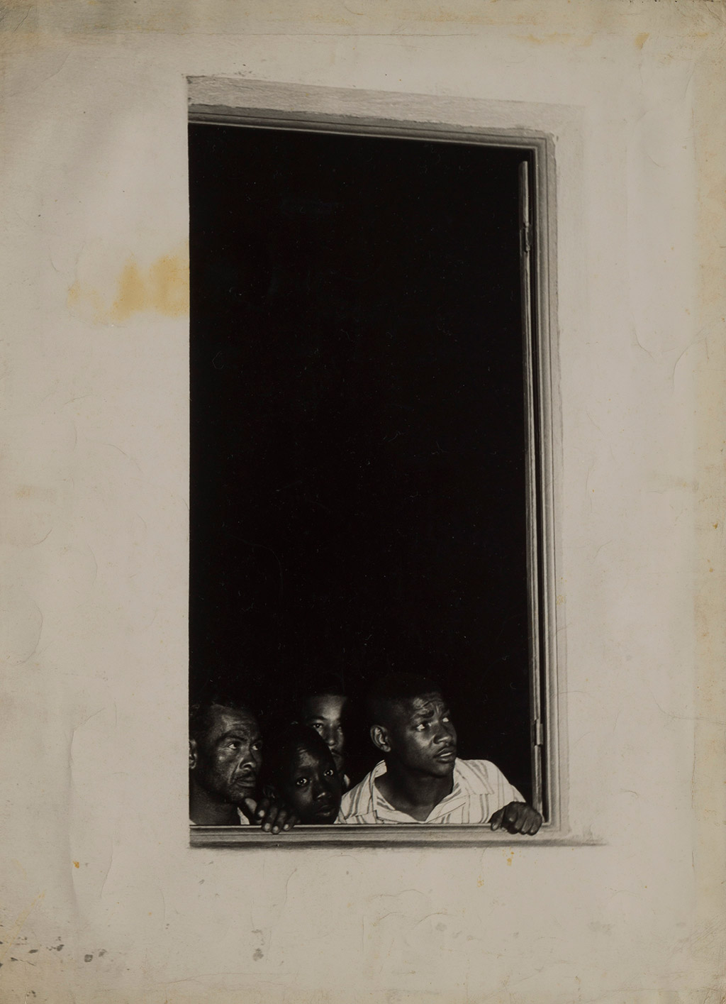 [Description: Black and white photograph of people looking out of a window]